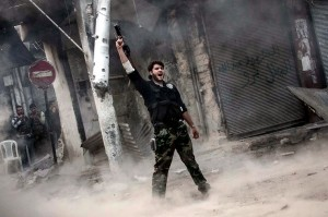 A fighter celebrates after firing a missile toward a building where Syrian troops were hiding. /Boston.com