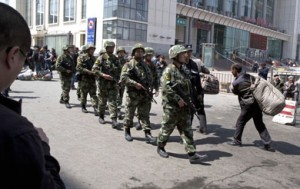 Heavily armed Chinese paramilitary police march past the site of the April 30 explosion outside the Urumqi South Railway Station.  /AP/Ng Han Guan