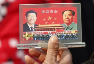 A Tiananmen Square street vendor displays a souvenir with pictures of Chinese President Xi Jinping and Chairman Mao Zedong.