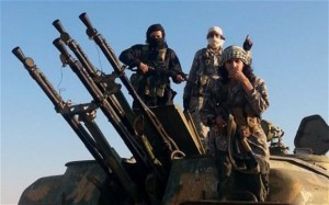 ISIL fighters on top of a captured military vehicle with anti-aircraft guns in Raqqa, Syria. /Raqqa Media Center/AP