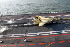 A J-15 fighter jet is slowed by an arresting device as it lands on the Liaoning aircraft carrier.  /Li Tang/China Daily