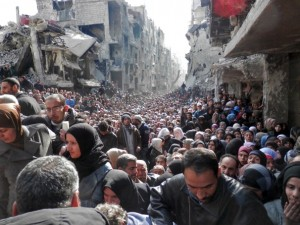 Syrians await humanitarian aid at the Yarmouk refugee camp. /United Nation Relief and Works Agency via Getty Images