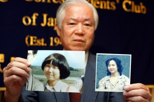 The father of Japanese abductee, Megumi Yokota, holds a picture of his daughter at 13 and then at 20 in North Korea. / Koichi Kamoshida / Getty