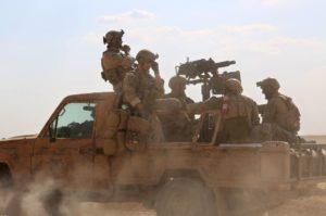 Armed men in uniform identified by Syrian Democratic forces as US special operations forces ride in a pickup truck in the village of Fatisah, in the northern Syrian province of Raqa on May 25. /AFP/Delil Souleiman
