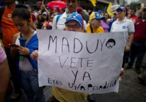 "A woman holds a sign with a message that reads in Spanish: ""Maduro leave already……you are a nightmare!"" during an opposition march in Caracas on May 14. /AP/Ariana Cubillos"