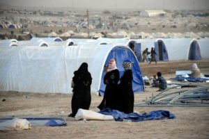 Displaced women wait for their tent to be built at a refugee camp west of Baghdad on June 21. /Nawras Aamer/EPA
