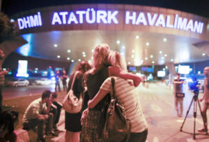 Passengers embrace each other at the entrance of Istanbul's Ataturk airport, early Wednesday, following their evacuation after a blast. /AP