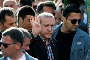 Turkish President Recep Tayyip Erdogan gives a four-finger gesture of solidarity with the Muslim Brotherhood during a funeral for a casualty of the thwarted coup. /Reuters
