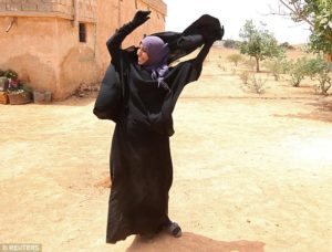 A woman is seen removing the ISIL-imposed full-face veil in Manbij. /Reuters