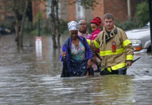 A member of the St. George Fire Department helps residents wade through floodwaters in Baton Rouge.