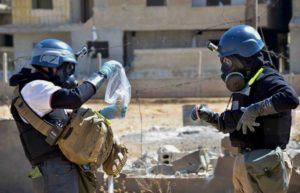 Investigators take samples from sand near a part of a missile that was suspected of carrying chemical agents near Ain Terma, Syria on Aug. 28, 2014. /AP