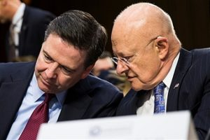 National Intelligence James Clapper (R) whispers to FBI Director James Comey during a Senate Intelligence Committee hearing in Washington, USA on February 9, 2016. /Getty Images