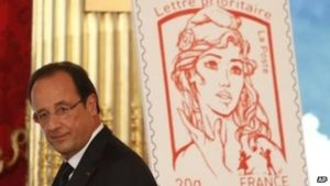 French President Francois Hollande stands next to the newly unveiled official Marianne postal stamp. /AP