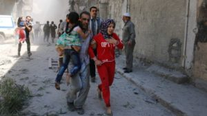Residents run for cover after a Syrian regime airstrike in Aleppo. /AFP
