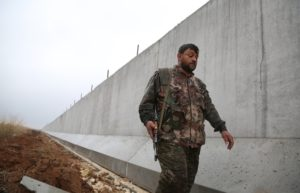A YPG fighter walks along the Turkish-Syria border wall. /AFP