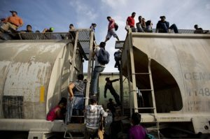 Central American migrants climb on a north bound train during their journey toward the U.S.-Mexico border. /AP