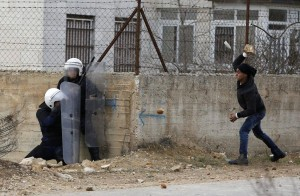 A Palestinian youth throws a stone at policemen outside the Jalazoun refugee camp near the West Bank city of Ramallah on Jan. 12.  /LENS/Mohamad Torokman