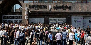 Gaza civil servants line up at a bank's ATM machine.  /AP