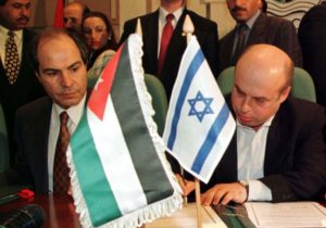 Israeli Trade Minister Natan Sharansky (R) signs an agreement to expand economic ties with Jordan while his Jordanian counterpart Hani Mulqi watches. /Reuters