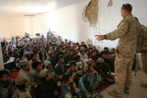 Marine Reserve Maj. Jason Brezler speaks with children attending school at the district center in Now Zad, Afghanistan, on Dec. 15, 2009. /1st Marine Division Public Affairs