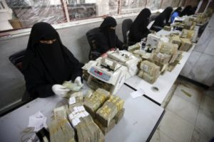 Money exchangers count stacks of Yemeni rials in of the Central Bank of Yemen in Sanaa. /Reuters