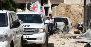 Vehicles from the International Committee of the Red Cross and the United Nations enter the rebel-held Syrian town of Daraya. /AFP/Getty Images