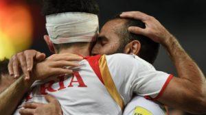 Syria's Omar Kharbin, left, hugs a teammate after scoring a goal. /AFP