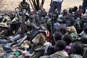 Boys sit with their rifles at a ceremony for demobilizing and reintegrating child soldiers in Pibor, South Sudan, on Feb. 10, 2015. /Samir Bol/Anadolu Agency/Getty Images