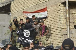 security forces raise an Iraqi flag as they hold a flag of the Islamic State group they captured in central Fallujah, Iraq, after fighting against the Islamic State militants, Friday, June 17. /AP