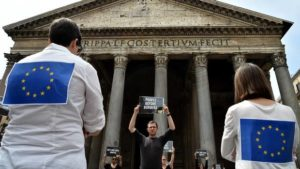"A man holds a placard reading ""people before borders"" next to people wearing European Union flags, in front of the Pantheon in Rome on June 20. /Getty Images"