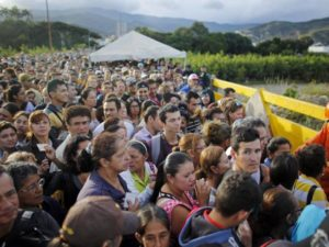 Venezuelans wait at the border to cross into Colombia. /AP