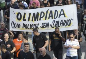 police officers protest with a banner that reads in Portuguese 'Olympics with unpaid police'. /AP