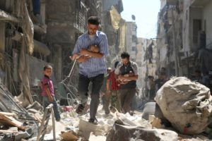 Men carry babies through the rubble of buildings in Aleppo destroyed in an airstrike. /AFP