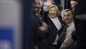 Democratic presidential candidate Hillary Clinton waves to members of the media while aboard her campaign plane. /AP