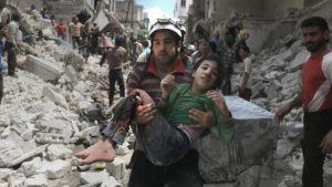 A man carries an injured child out of the rubble after an airstrike on a hospital in eastern Aleppo. /Getty Images