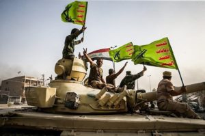 Fighters raise the flags of Iraq and the Popular Mobilization Forces.