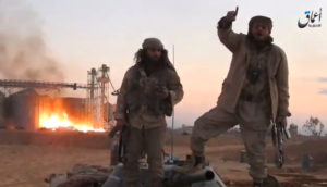 A still image taken from a video released by Islamic State-affiliated Amaq news agency, said to be in Palmyra, on December 11, 2016, purports to show Islamic State fighters in front of silos on fire and said to have been taken over by them. /Handout via Reuters