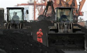 An employee walking between front-end loaders, which are used to move coal imported from North Korea at Dandong port in China. /Reuters