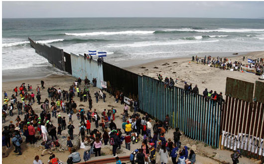 Members of a caravan of migrants from Central America and supporters gather on both sides of the border fence between Mexico and the U.S. as part of a demonstration, prior to preparations for an asylum request in the U.S., in Tijuana